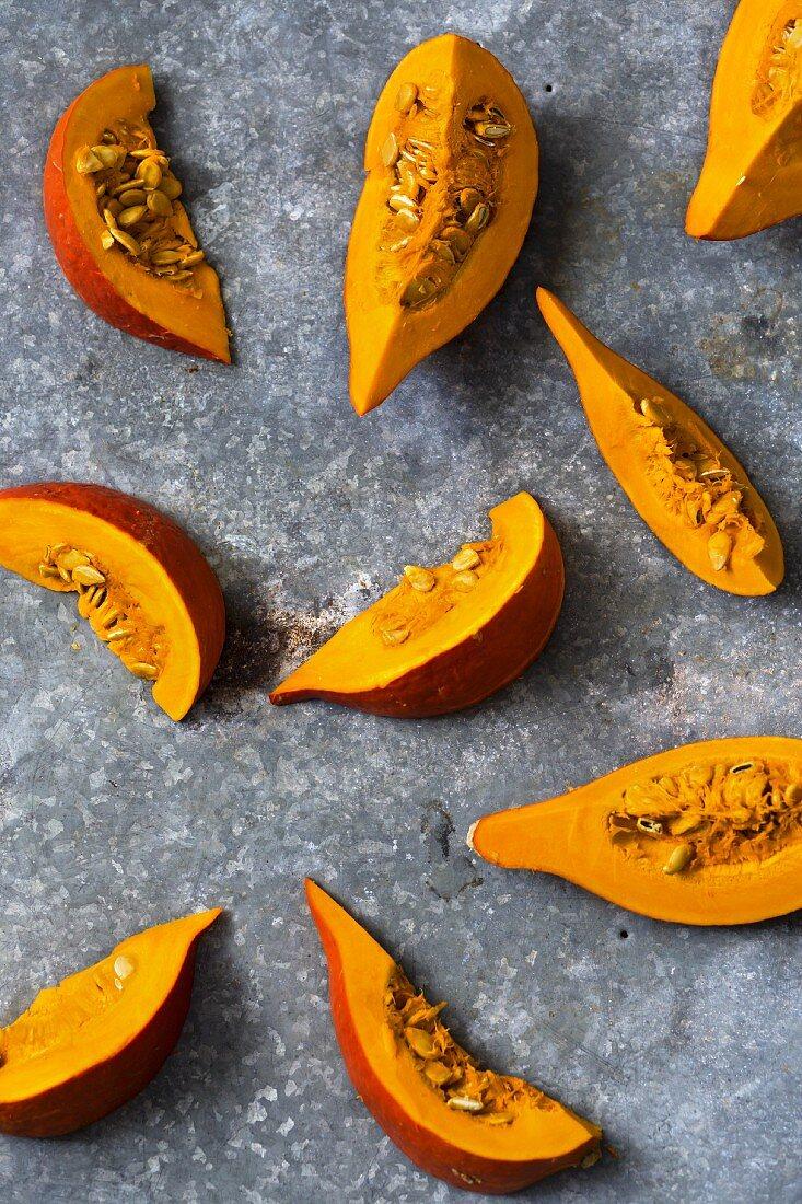 Hokkaido pumpkin wedges on a metal surface
