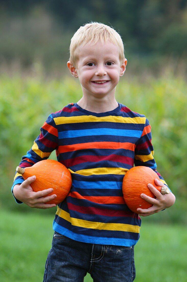 A blond boy in a garden holding two pumpkins