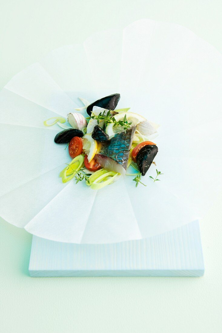 Fish and mussels with leek and tomatoes on parchment paper