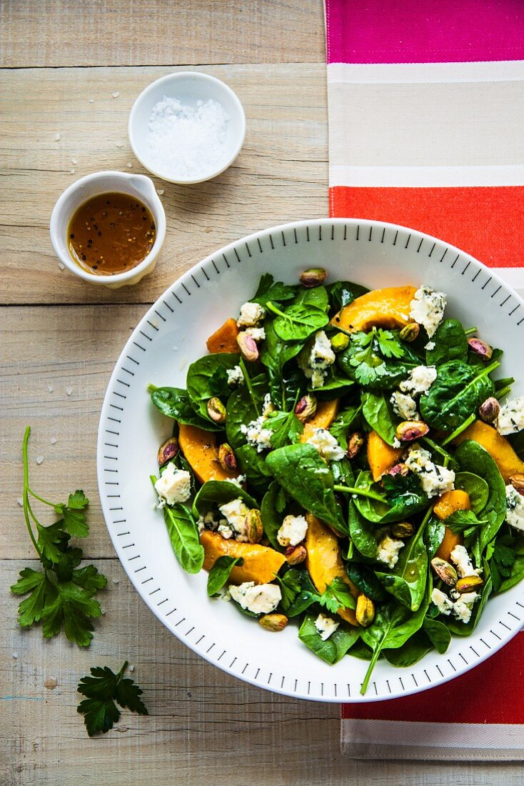 Spinach salad with poached quinces, blue cheese and pistachios