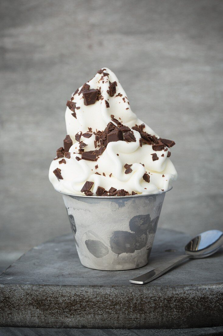 Frozen yoghurt in a metal cup with grated chocolate