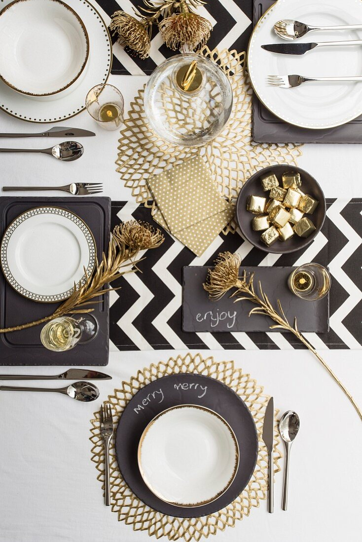 Festively set table in black, white and gold (top view)