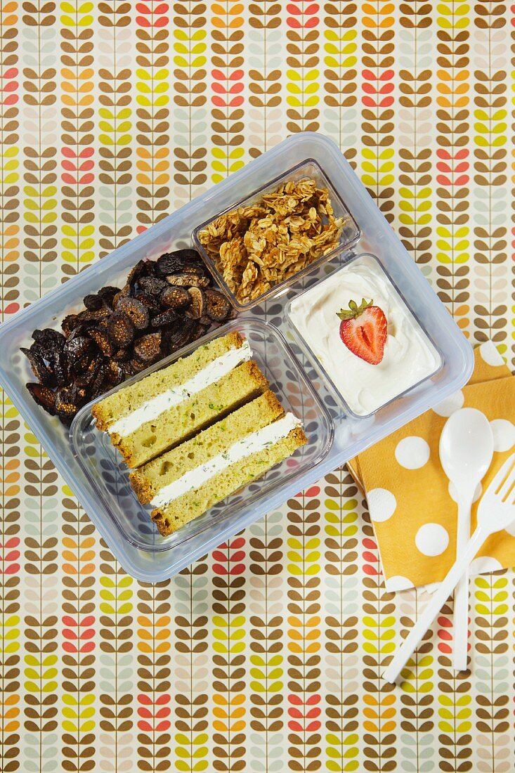 A sandwich, dried fruit, crunching muesli and a yoghurt in a plastic box