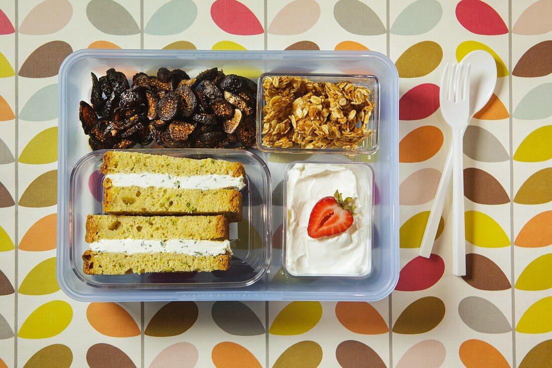 A sandwich, dried fruit, crispy muesli and yoghurt in a plastic box