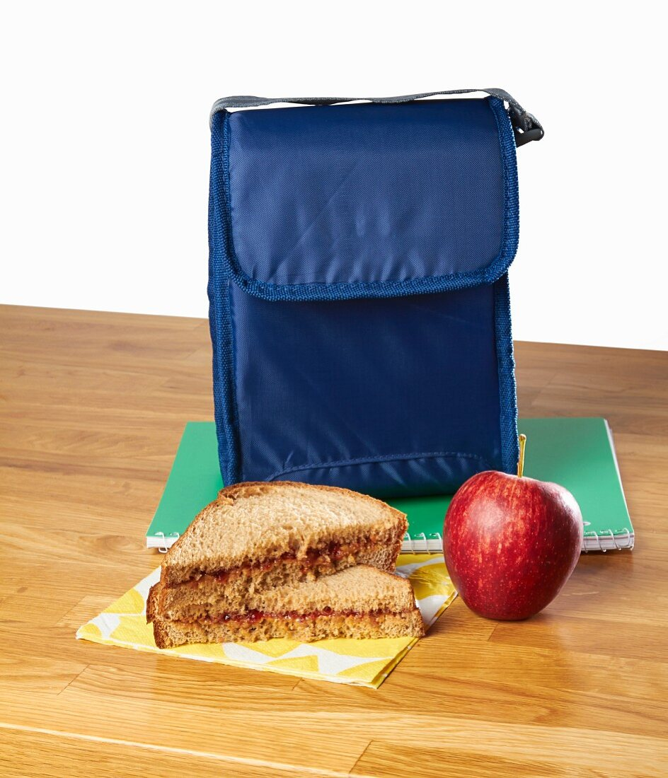 A peanut butter sandwich and an apple as a snack with a lunch bag