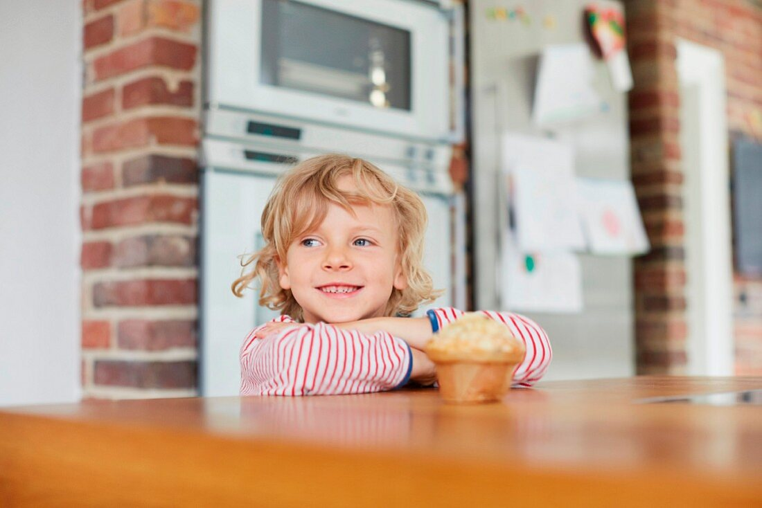 A boy standing at a kitchen table with a muffin in front of him