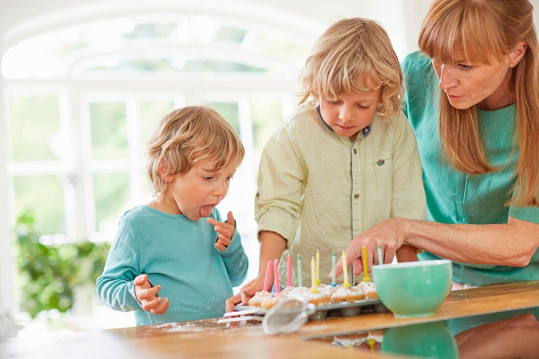 A mother and sons decorating birthday muffins on a kitchen table