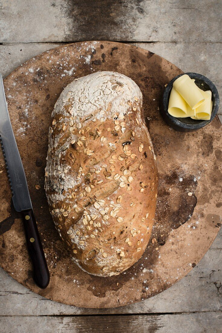A whole loaf of wholemeal bread on a baking stone with a butter dish