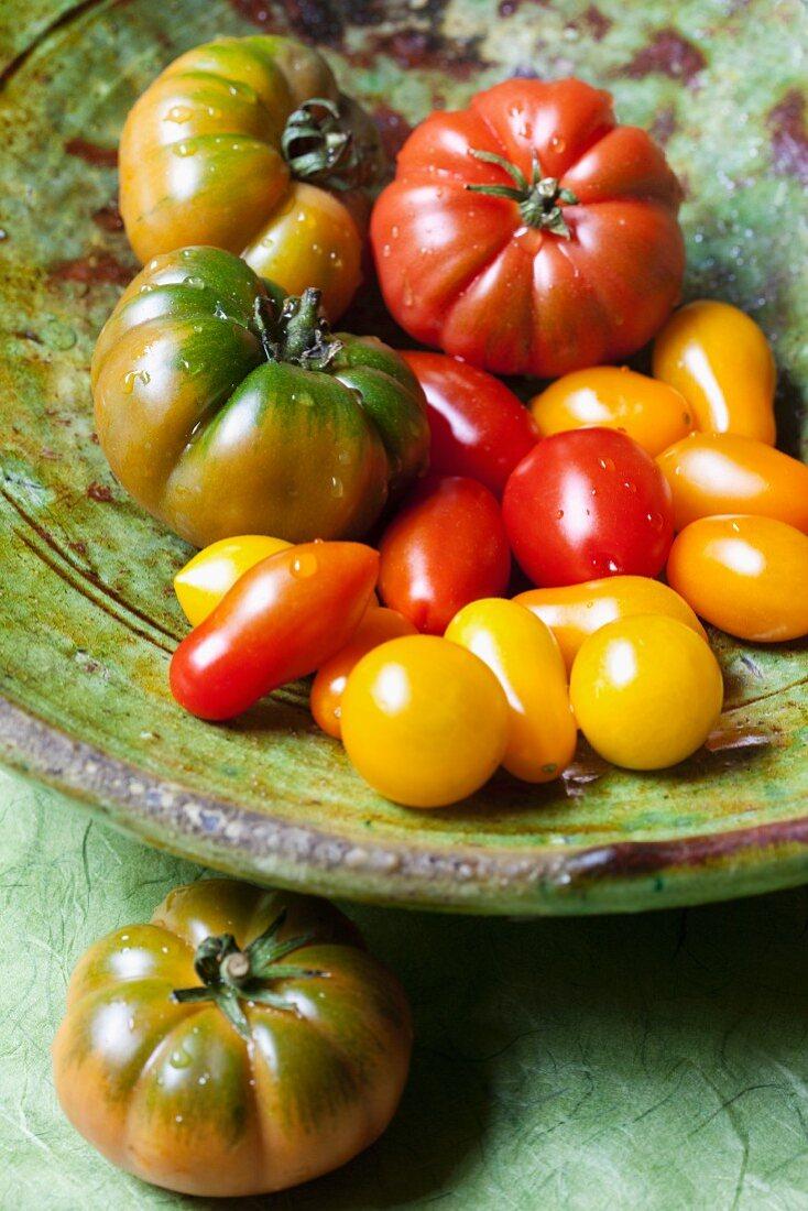 Various organic tomatoes in a ceramic bowl