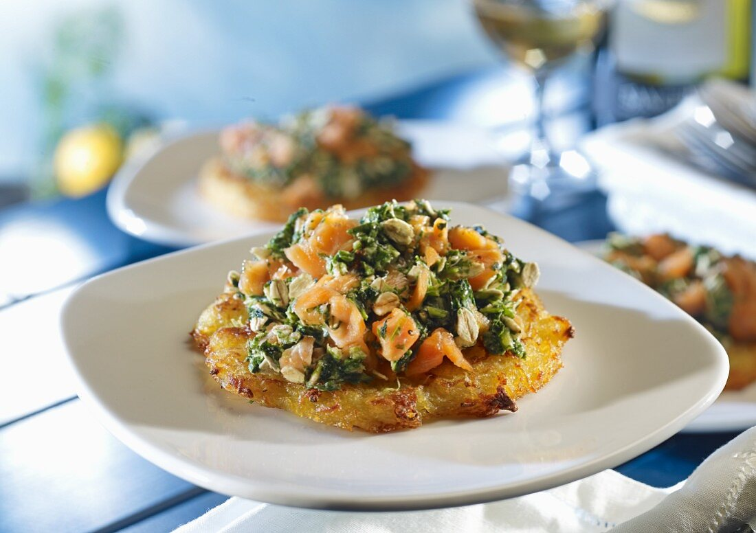 A potato fritter topped with salmon and spinach