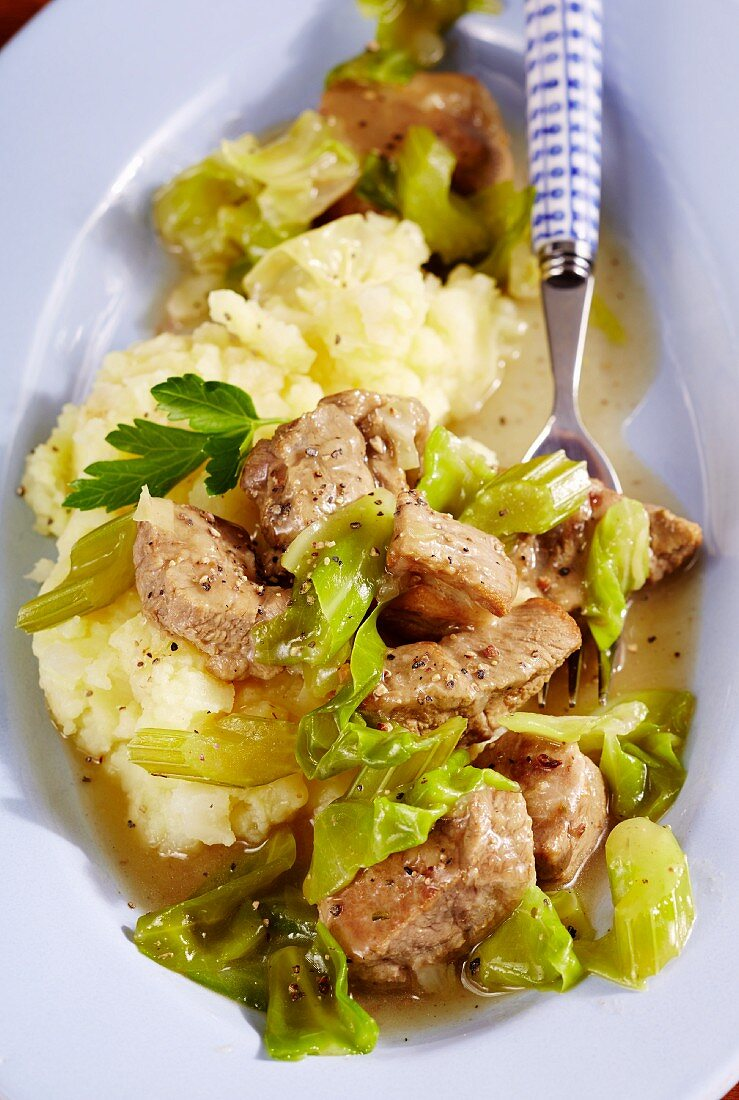 Pork goulash with pointed cabbage on a bed of mashed potatoes