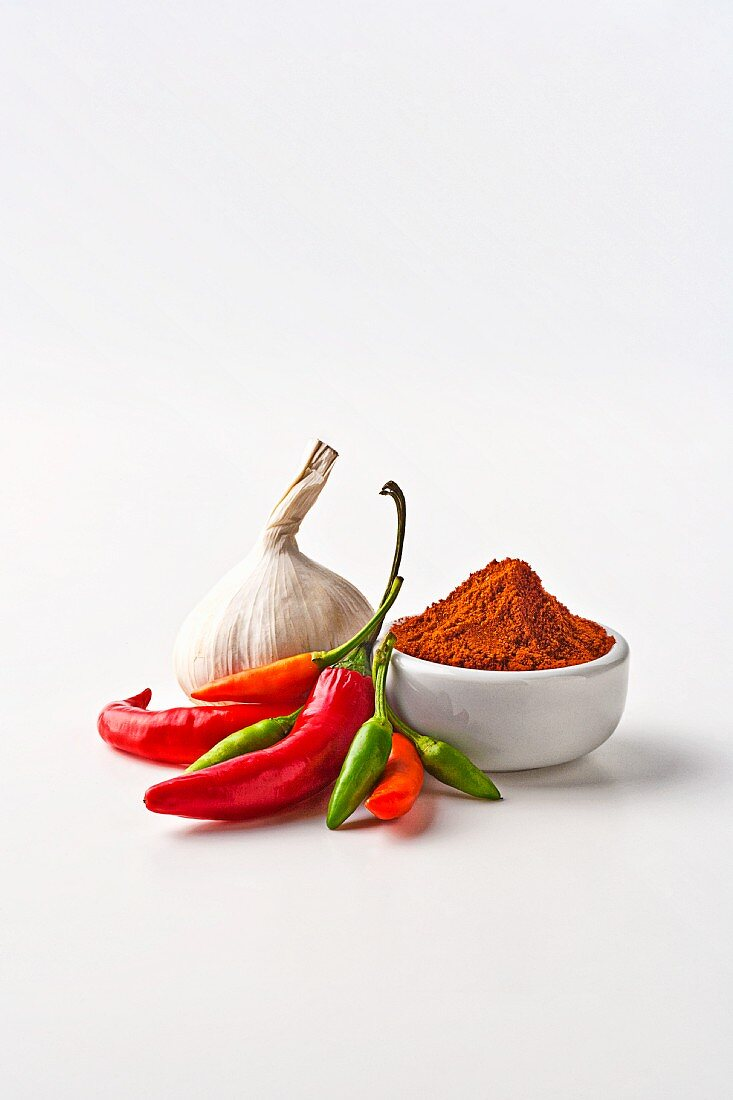 A bulb of garlic, chilli peppers and chilli powder on a white surface