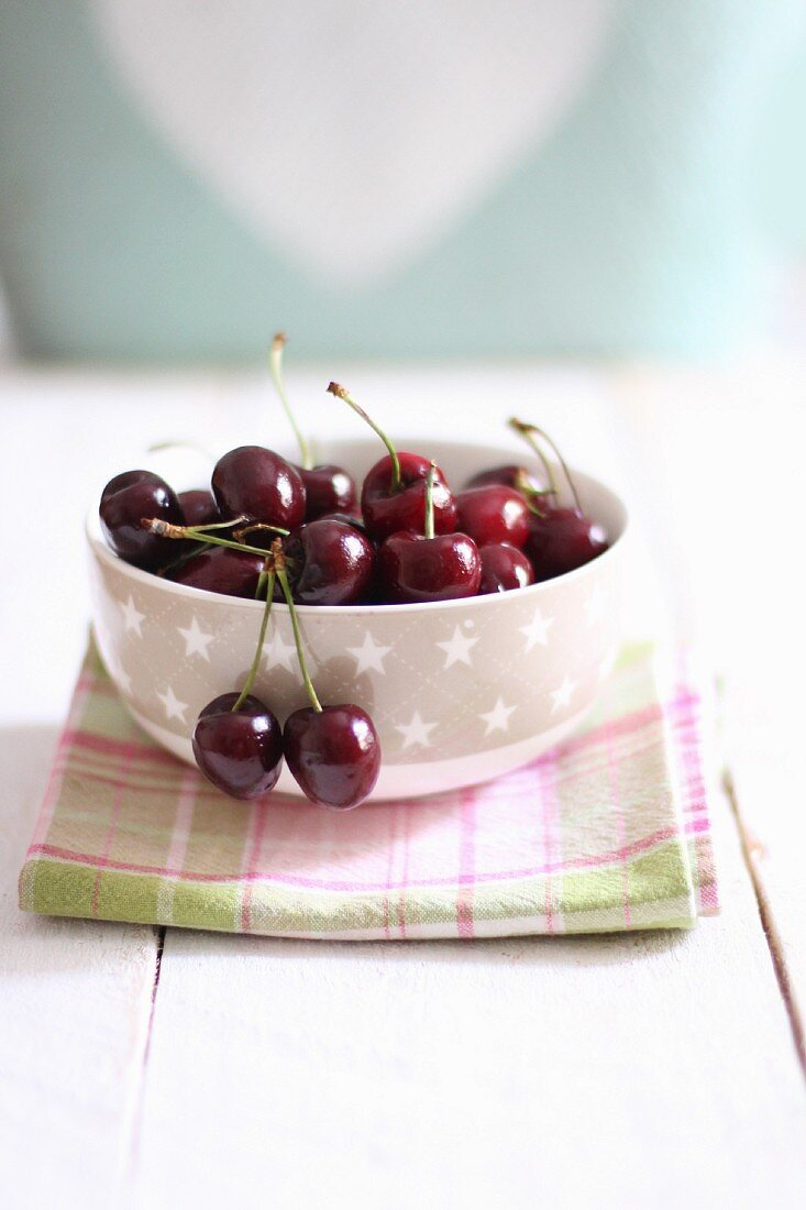 Fresh cherries in a bowl on a tea towel