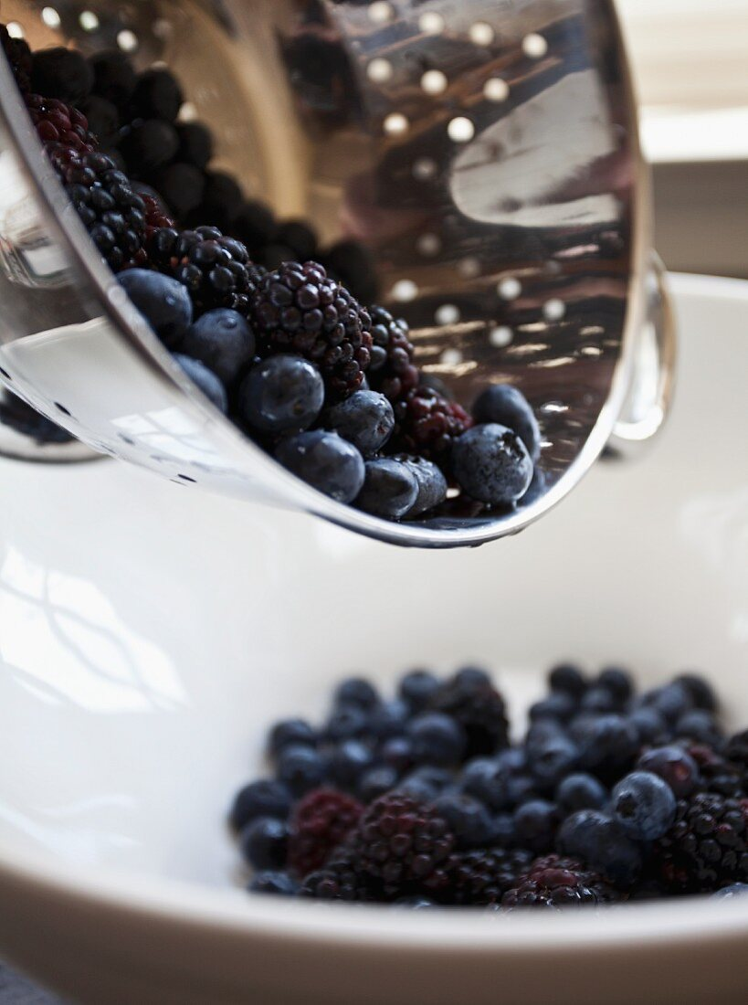 Freshly washed blackberries and blueberries being tipped from a colander into a bowl
