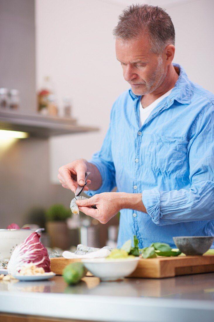 A man gutting a prawn