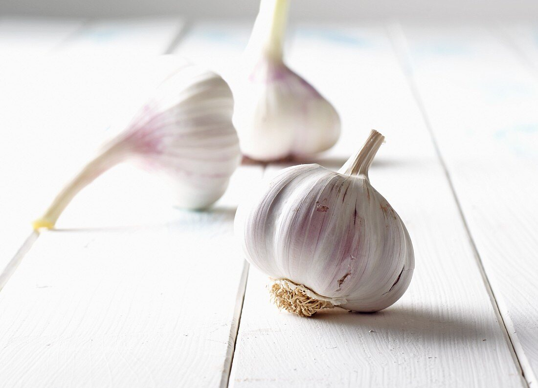 Three bulbs of garlic on a white wooden surface
