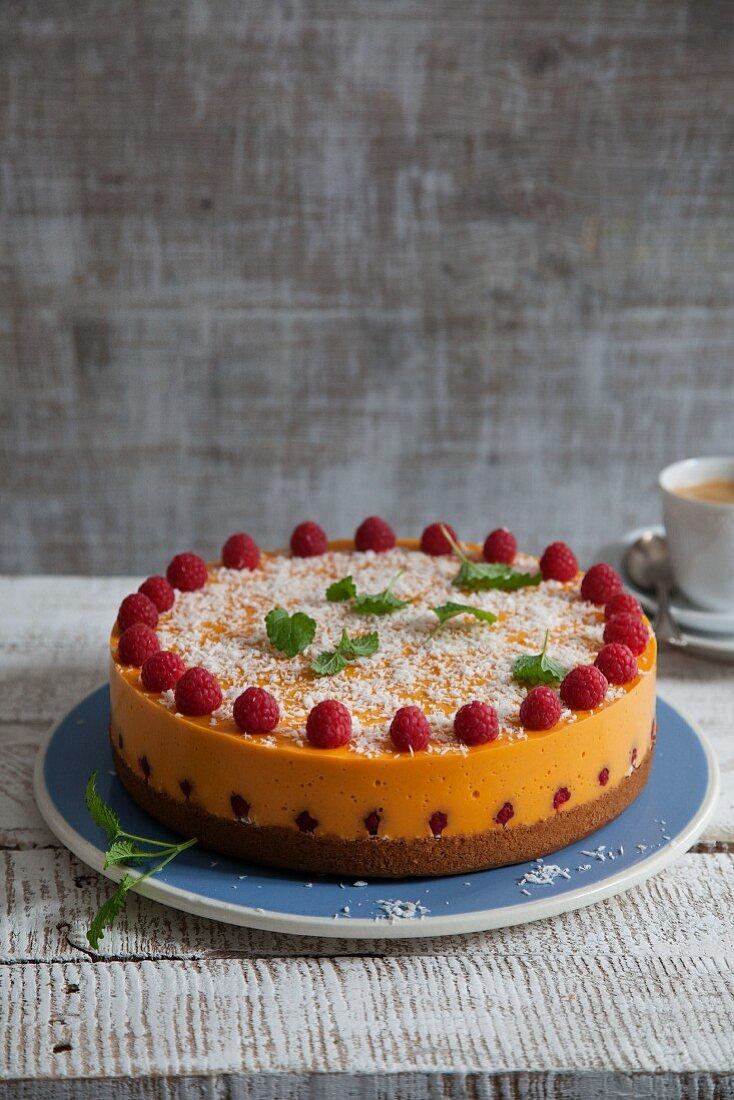 Vegan mango and papaya cake with coconut and fresh raspberries