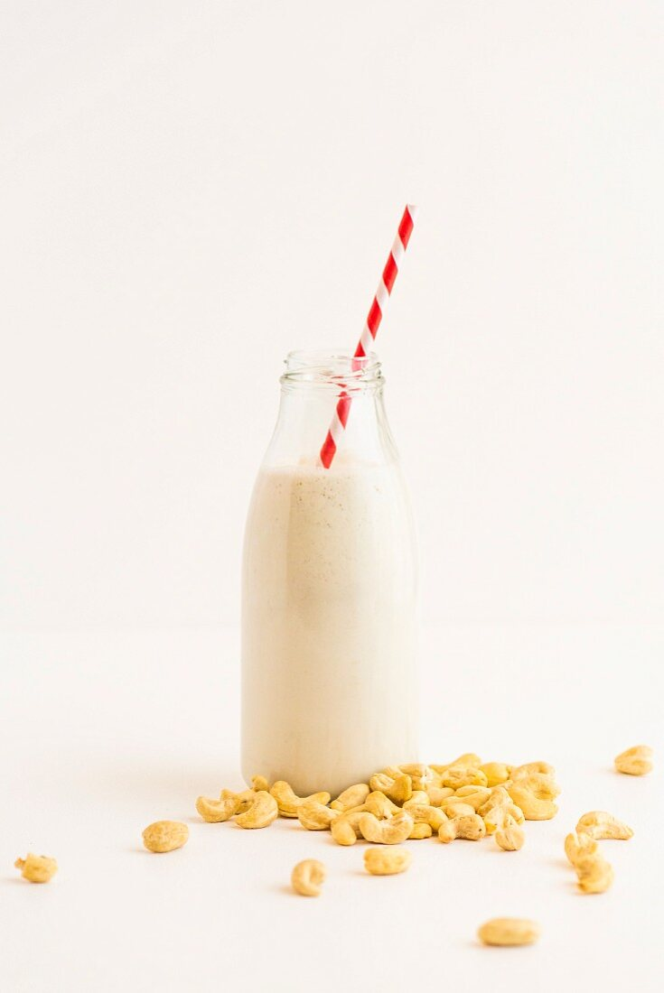Cashew nuts and a bottle of cashew nut milk with a straw