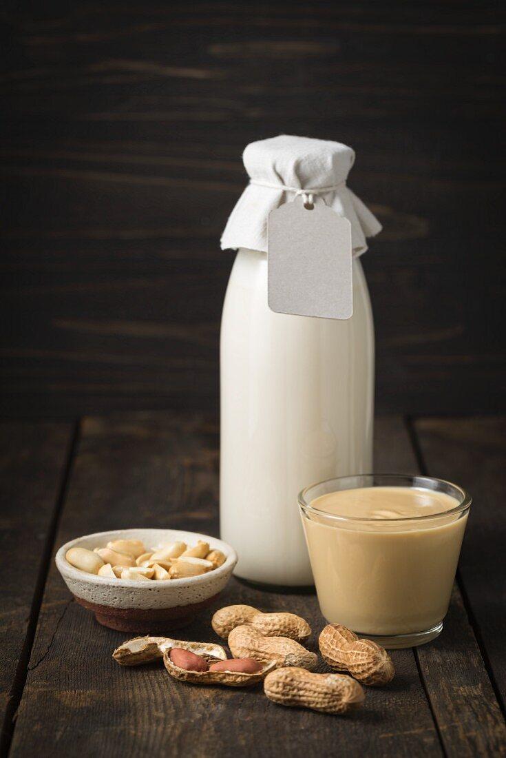Erdnussmus im Glas und Erdnussmilch in einer Glasflasche