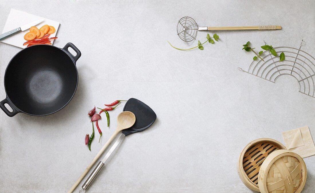 An arrangement of various utensils around a wok