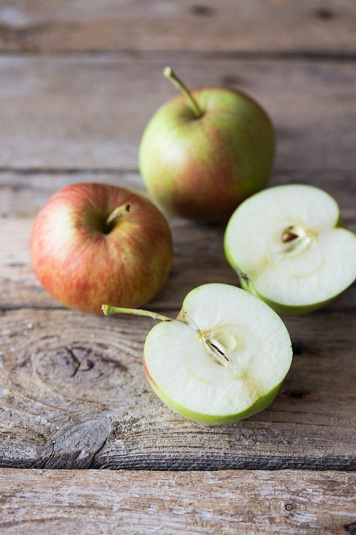 Apples, whole and halved, on a wooden surface