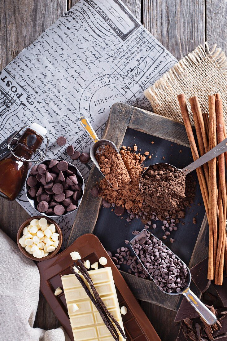 An arrangement of chocolate featuring chocolate chip, cocoa, syrup, vanilla pod and cinnamon sticks