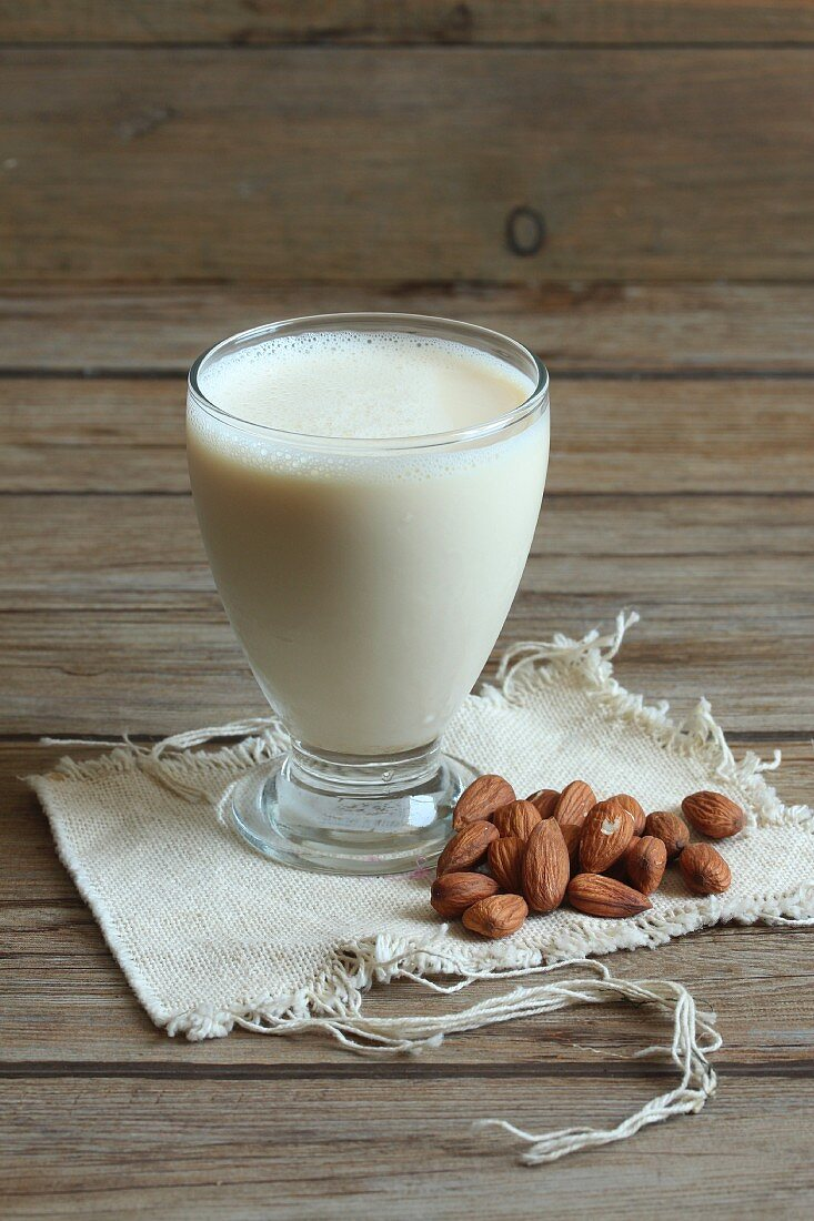 A glass of almond milk with almonds next to it