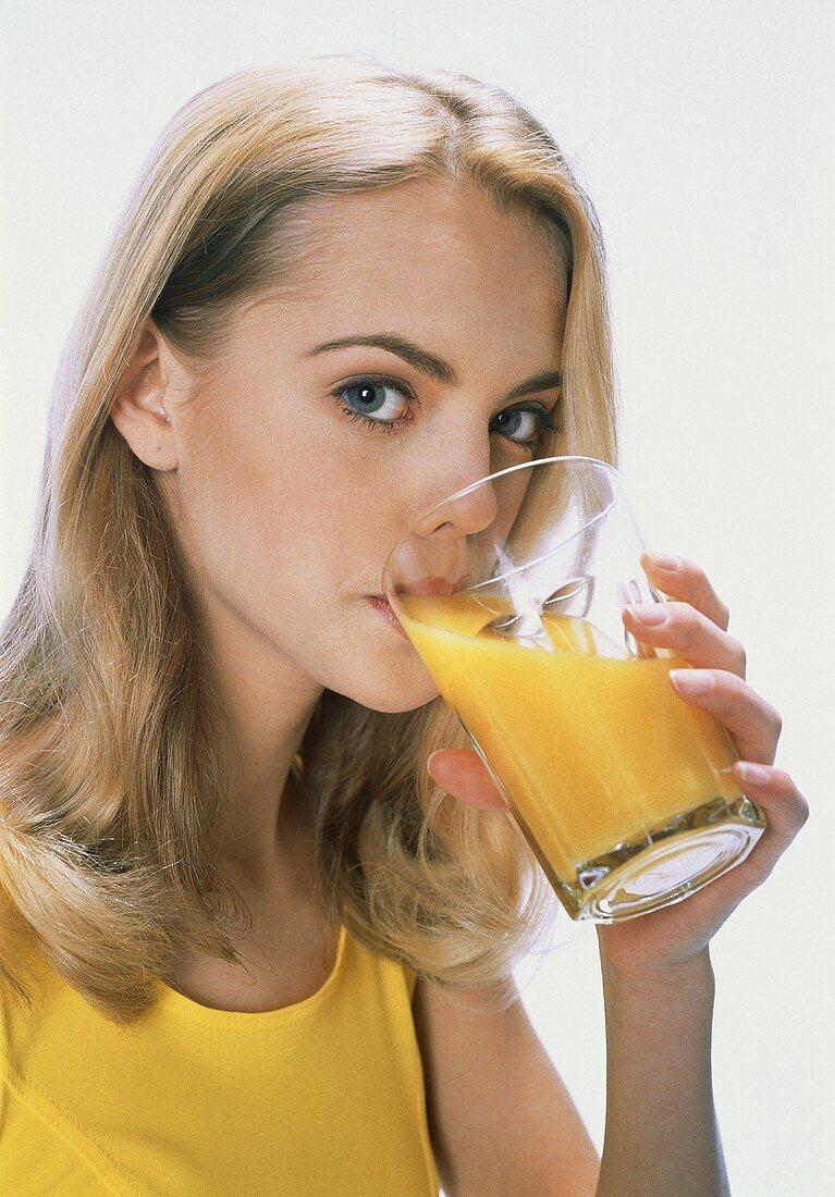 Blond woman drinking orange juice