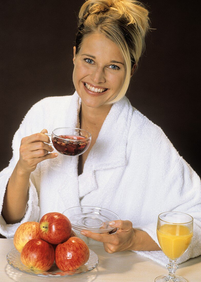 Smiling blond woman with a glass cup of fruit tea