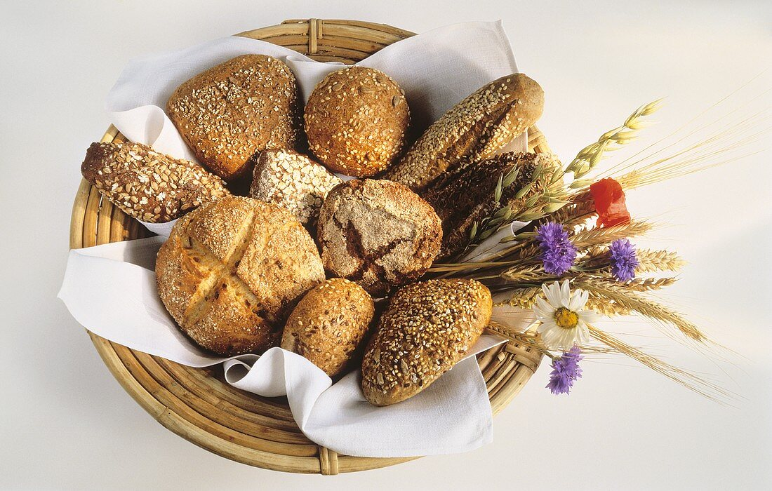 Wholemeal rolls in basket (grain baguettes and rolls)