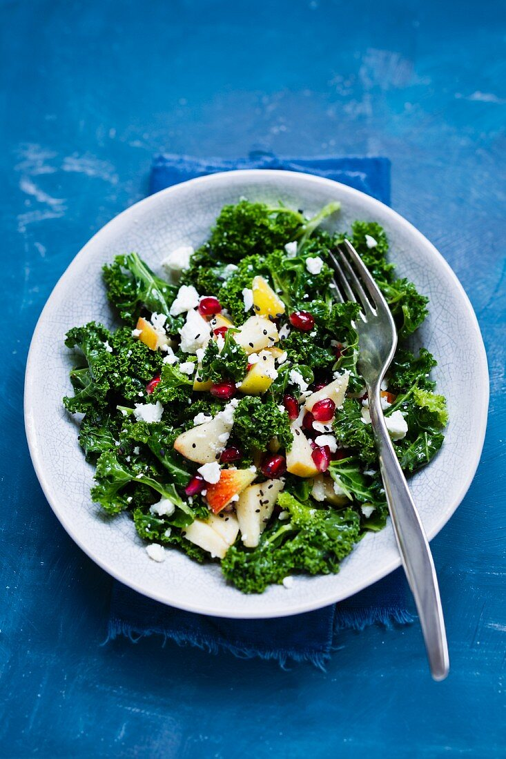 Kale salad with pomegranate, sheep's cheese, and apple