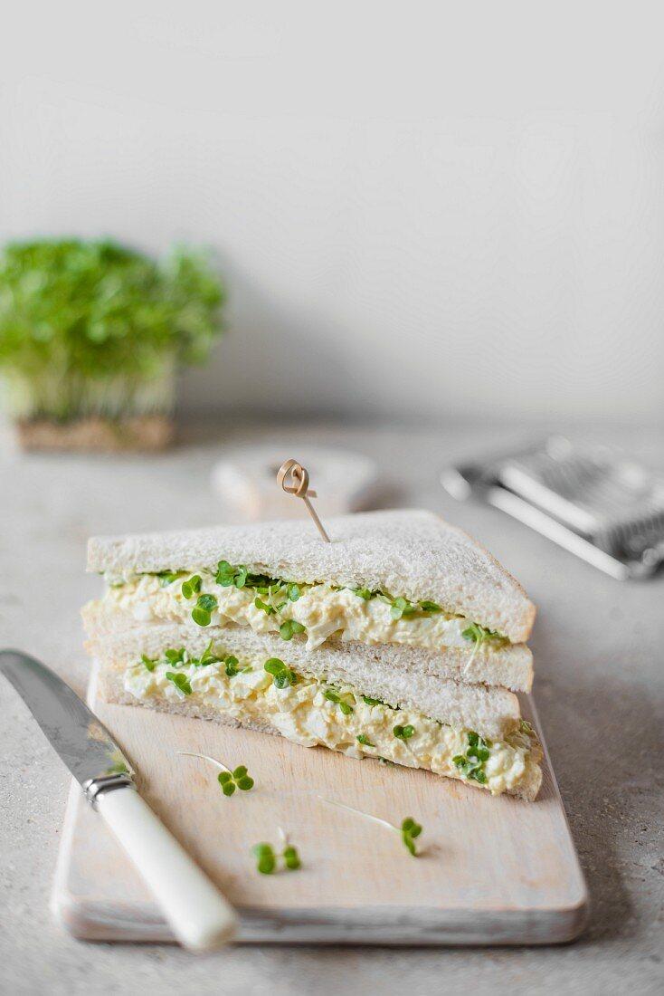 Sandwiches mit Eieraufstrich und Kresse auf Schneidebrett