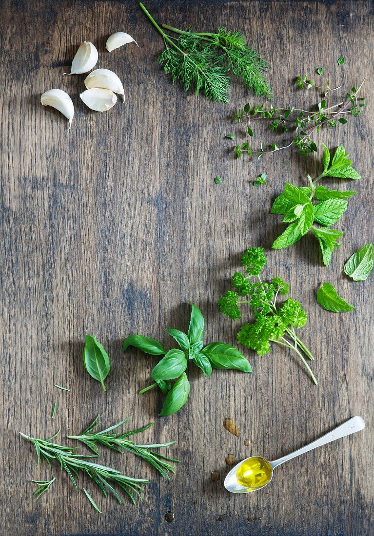 Rosemary, basil, parsley, mint, thyme and dill with garlic cloves and a spoon of olive oil