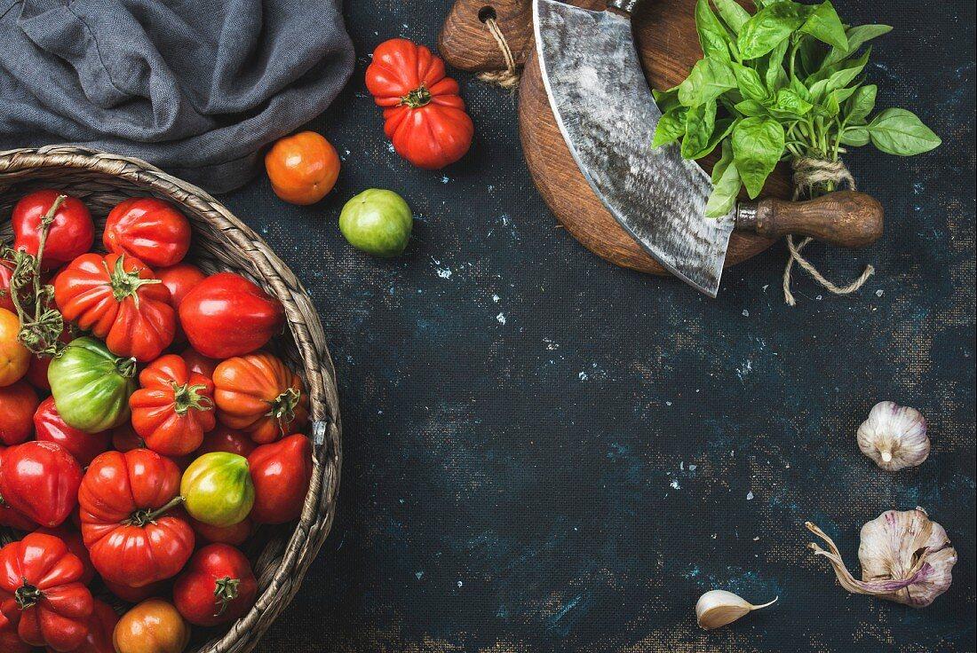 Fresh colorful ripe Fall heirloom tomatoes in basket, green basil leaves, garlic and herb chopper knife