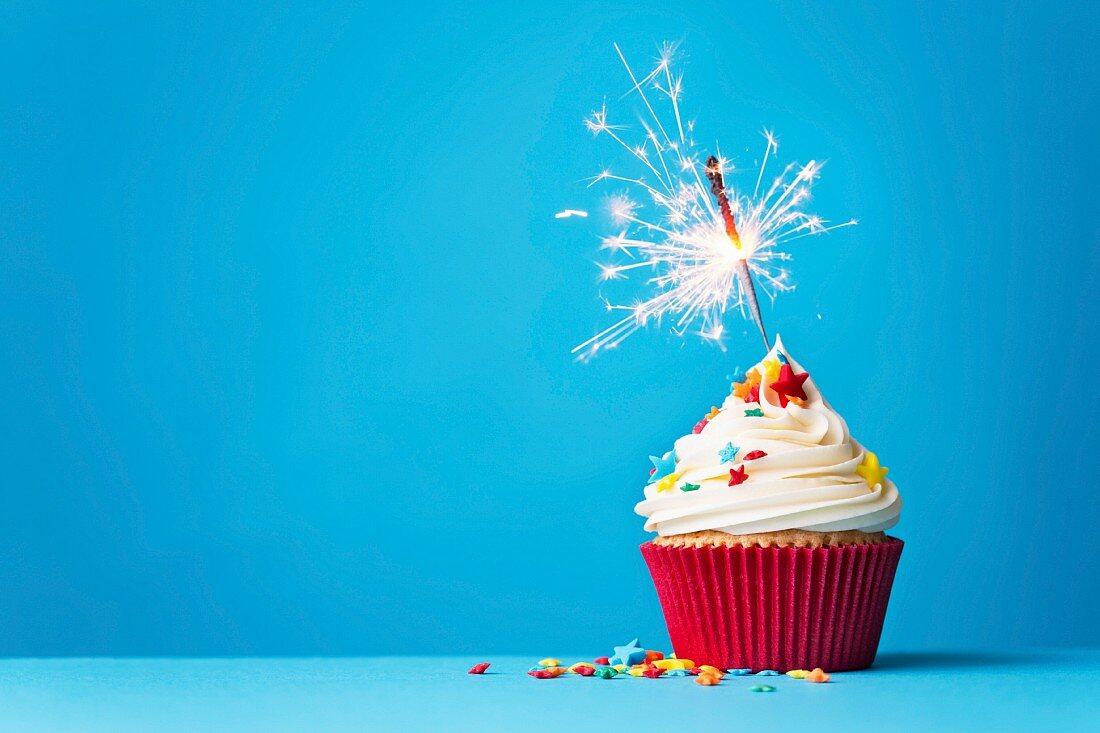 Cupcake mit Wunderkerze vor blauem Hintergrund