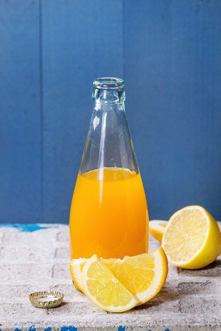 Opened glass bottle of citrus orange and lemon lemonade
