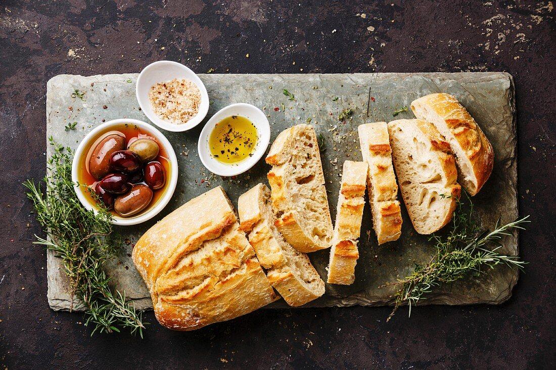 Fresh Ciabatta bread sliced on stone slate board with olives, oil, salt and herbs on dark background
