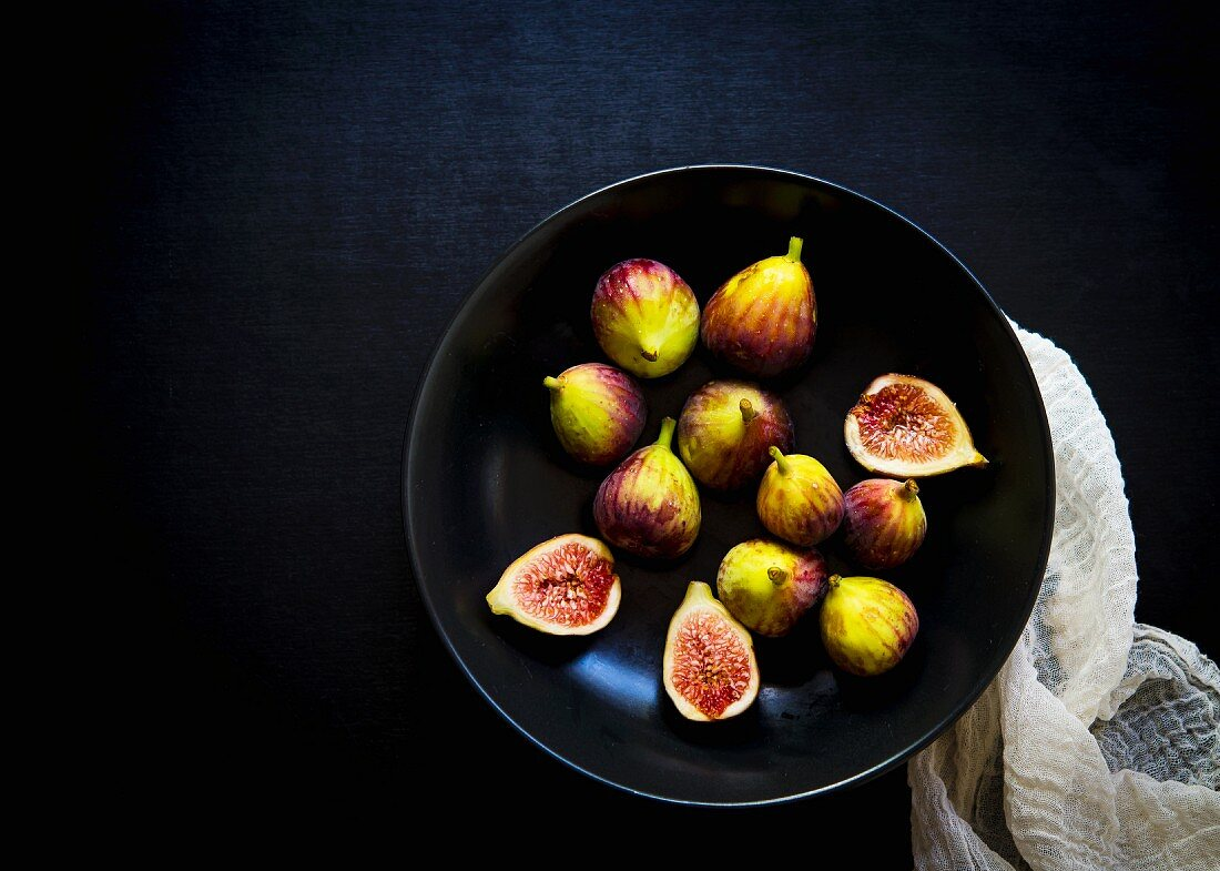 Whole and cut fresh figs in a black bowl