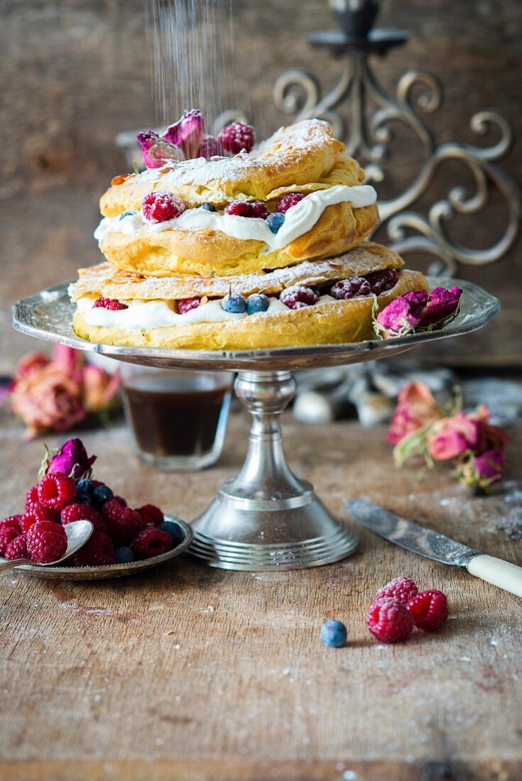 A two-tier choux pastry Paris Brest cake with cream and fresh berries