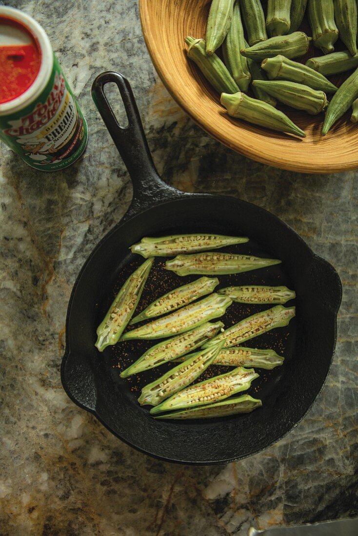 Fried okra halves in a cast iron pan