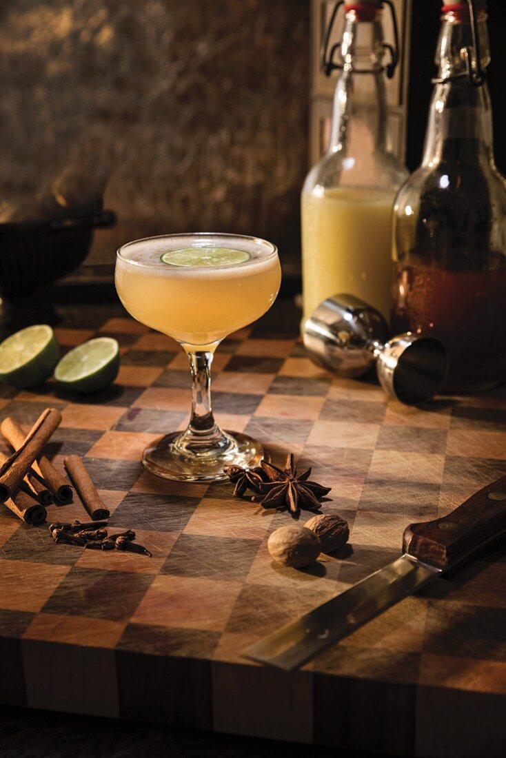 A spicy ginger cocktail garnished with a slice of lime and surrounded by star anise, cinnamon, cloves and nutmeg