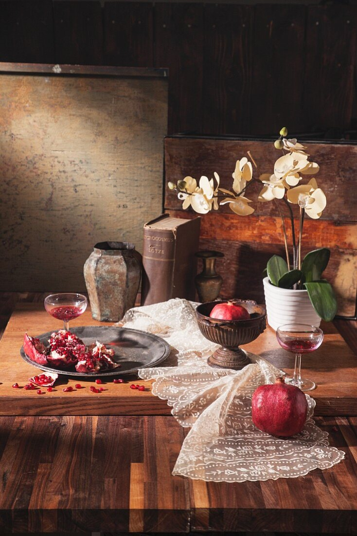 Pomegranate drinks with fresh pomegranate, a lace cloth, a book and a white orchid