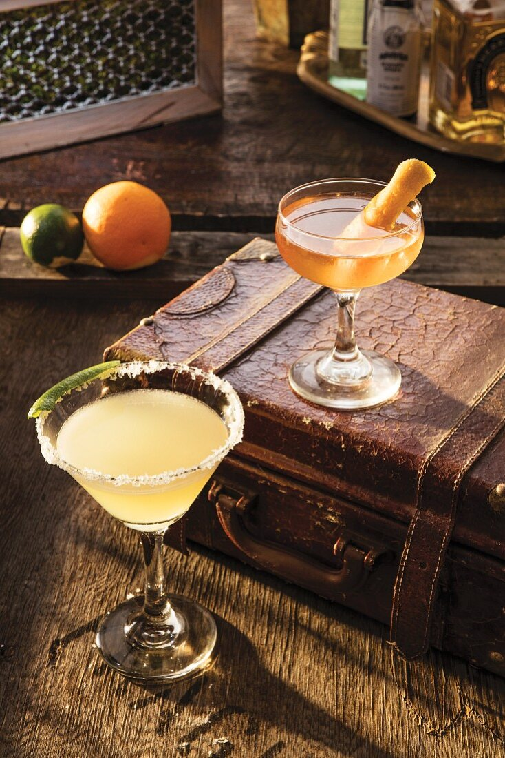 A Margarita cocktail and a Manhattan cocktail on an old suitcase