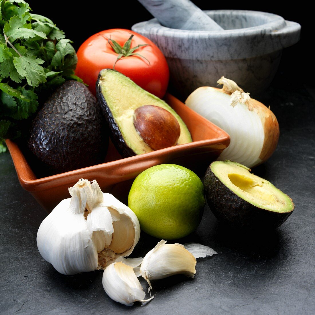 Ingredients for guacamole: avocado, onion, tomato, garlic and coriander