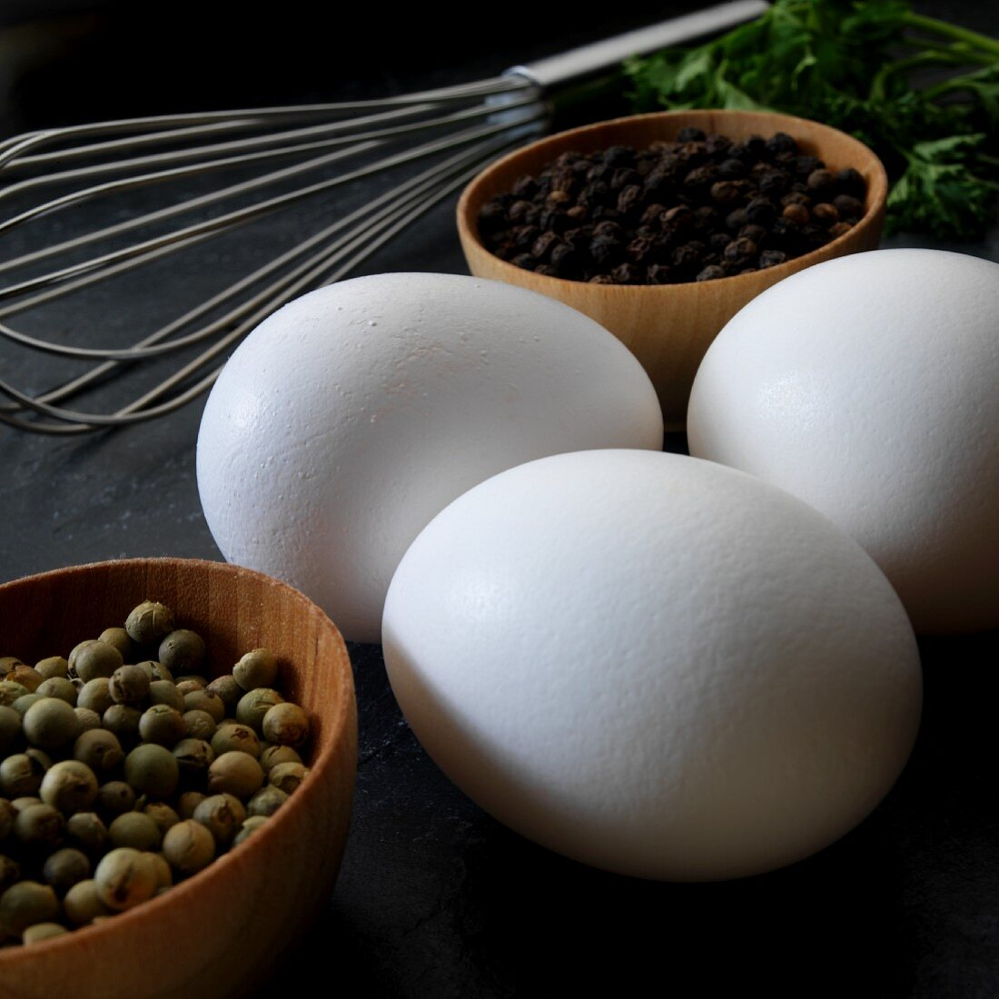 An arrangement of eggs, peppercorns and a whisk (close-up)