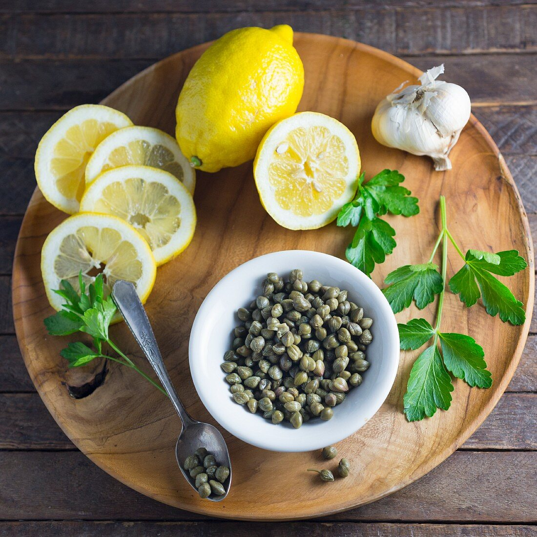 Lemons, capers, garlic and parsley on a wooden plate