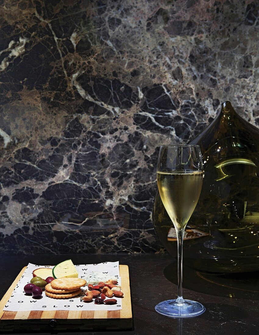 Glass of Champagne in front of spherical vase and marble wall