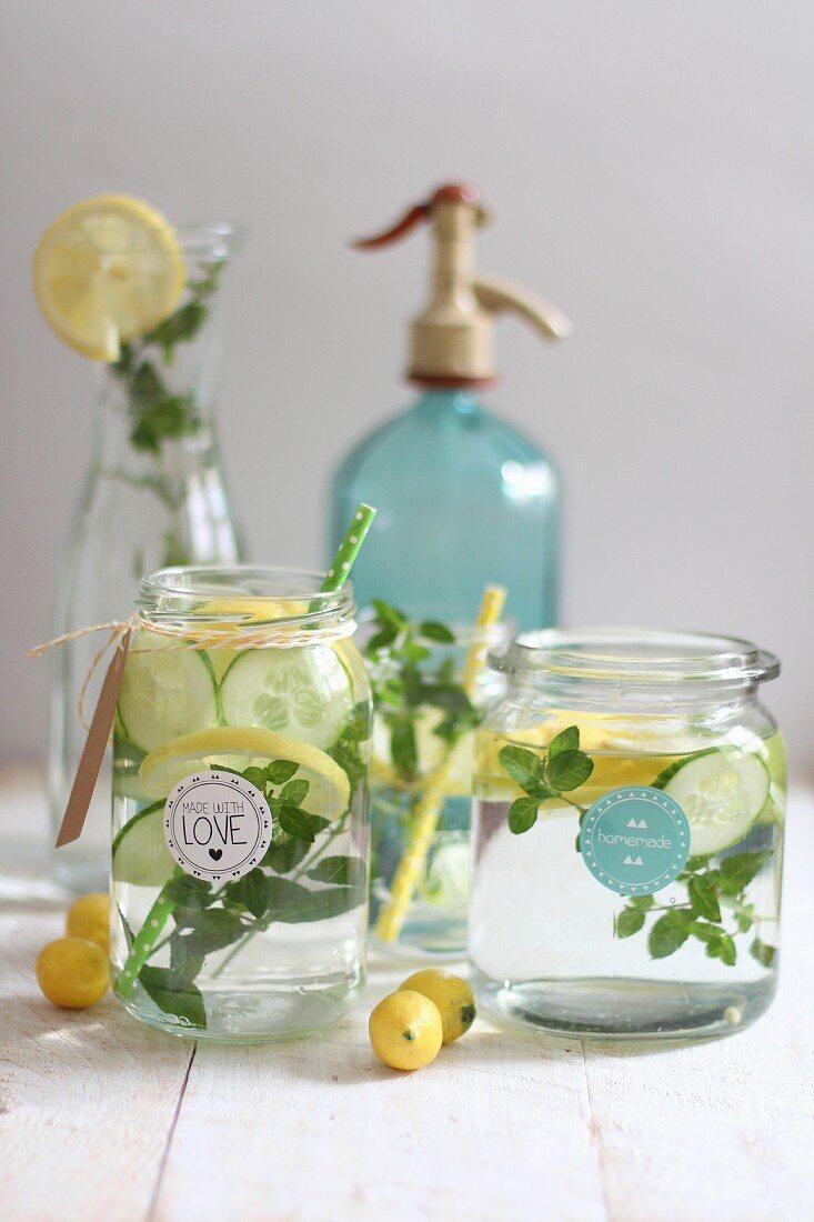Wasser aromatisiert mit Gurken, Zitronen und Kräutern in Glasgefässen