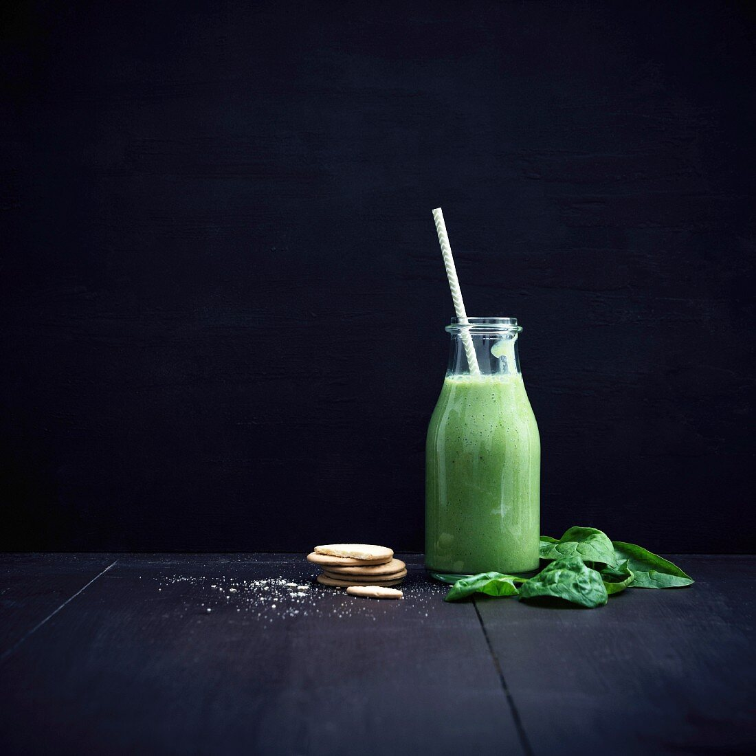 Vegan green smoothie with leaf spinach in a glass bottle