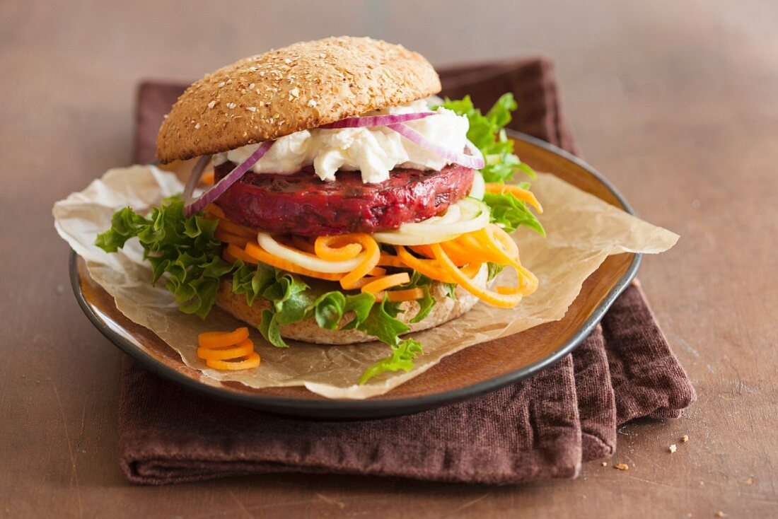 A veggie burger with a beetroot patty, goats' cheese and vegetable spirals